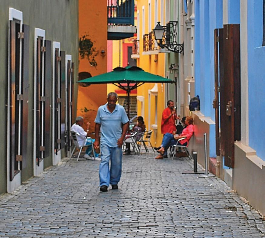[IMAGE DESCRIPTION: Man walks down an alley surrounded by colorful buildings in Puerto Rico.]