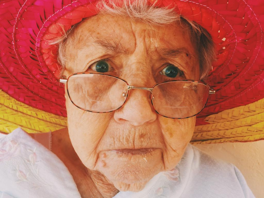 Grandmother with colorful hat staring into camera