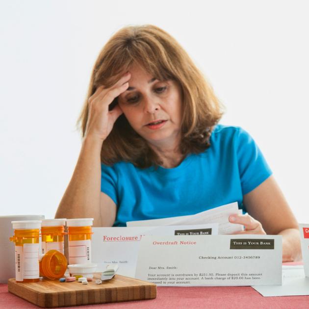 Woman with prescription drug bottles and medical bills
