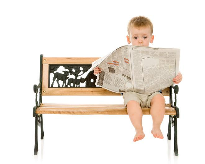 toddler boy sitting on a bench reading a newspaper